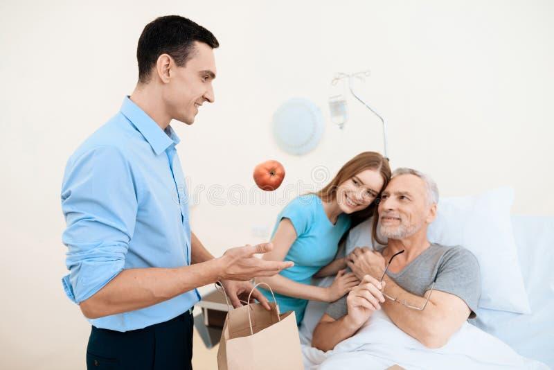 Een bejaarde ligt in een het ziekenhuisruimte op een bed Hij wordt gezien door een man met een vrouw De vrouw koestert de oude ma royalty-vrije stock foto