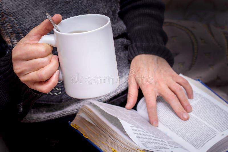 Een bejaarde met een in hand kop thee leest een boek Het lezen van Bible_ royalty-vrije stock afbeelding