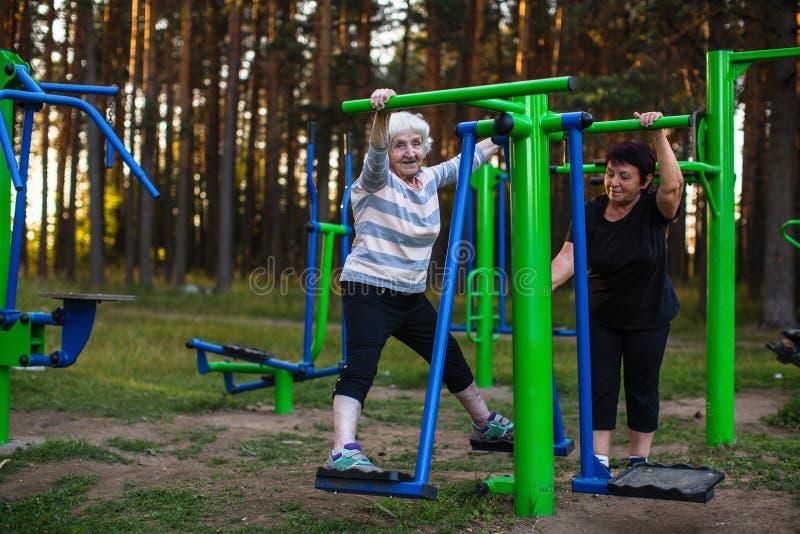 Een bejaarde met een volwassen dochter doet oefeningen op de sportspeelplaats stock afbeeldingen