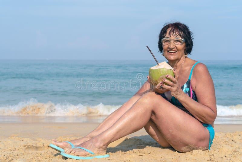 Een bejaarde met zwart haar zit door het overzees op een zonnige dag Een vrouw in een badpak met een kokosnoot glimlacht royalty-vrije stock afbeeldingen