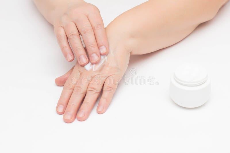 Een bejaarde past de room op de problematische huid van de handen van irritatie en roodheid op de huid toe, room stock foto's