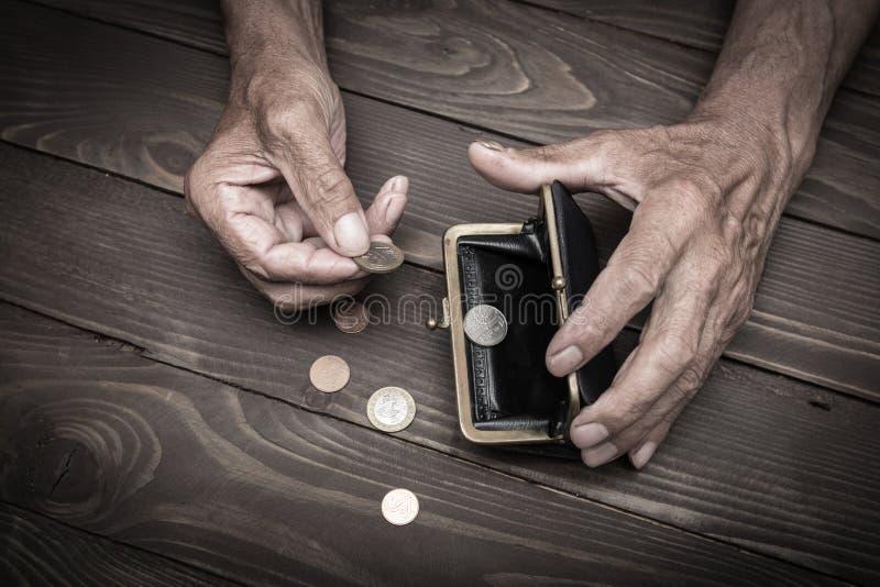 Een bejaarde persoon houdt de muntstukken over de oude lege portefeuille E royalty-vrije stock foto