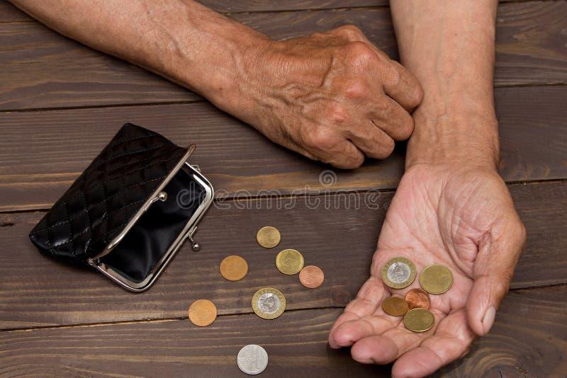Een bejaarde persoon houdt de muntstukken over de oude lege portefeuille royalty-vrije stock fotografie