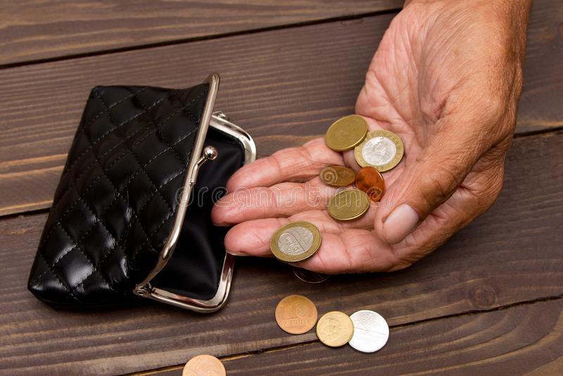 Een bejaarde persoon houdt de muntstukken over de oude lege portefeuille Het concept armoede in pensionering stock foto