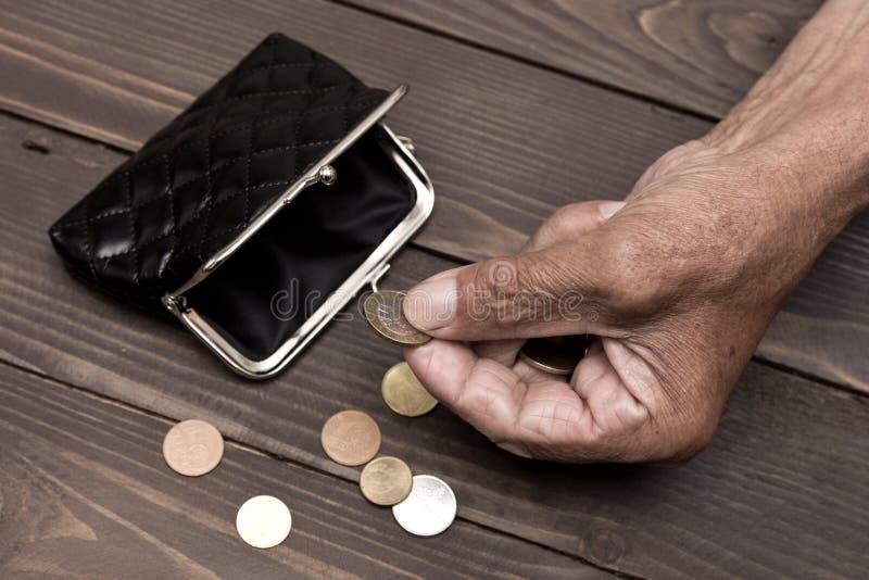 Een bejaarde persoon houdt de muntstukken over de oude lege portefeuille Het concept armoede in pensionering stock foto's