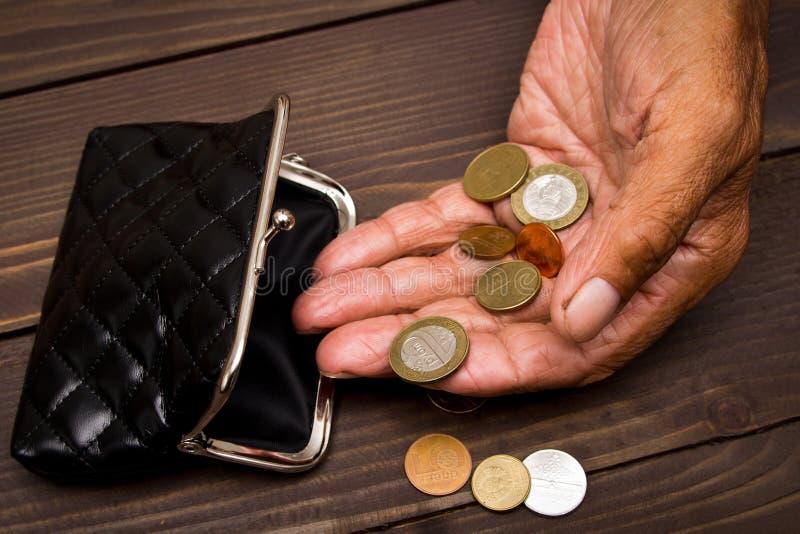 Een bejaarde persoon houdt de muntstukken over de oude lege portefeuille Het concept armoede in pensionering stock afbeeldingen