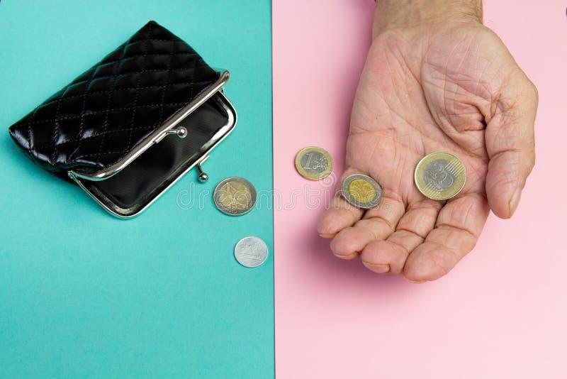 Een bejaarde persoon houdt de muntstukken over de oude lege portefeuille Het concept armoede in pensionering royalty-vrije stock afbeelding
