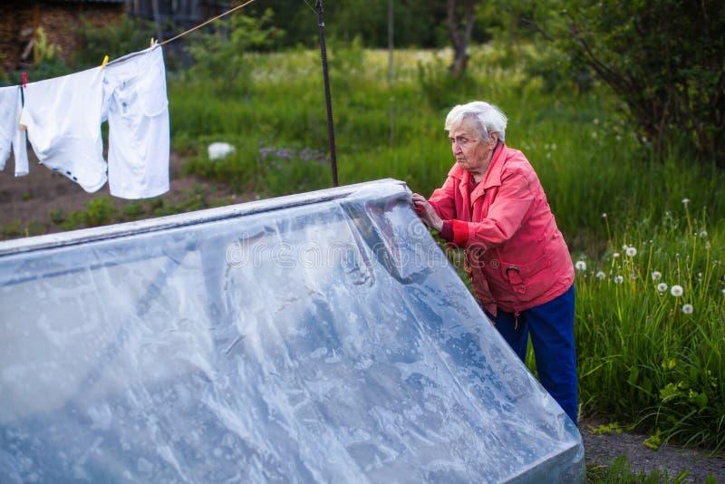 Een bejaarde sluit de serre dichtbij haar huis stock afbeeldingen