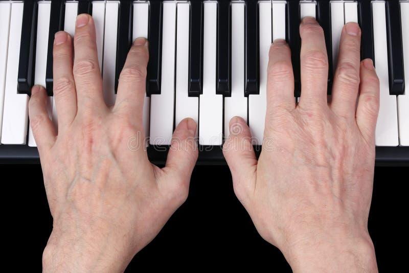 Een bejaarde teruggetrokken mens speelt een oude melodie op het toetsenbord van Th royalty-vrije stock foto