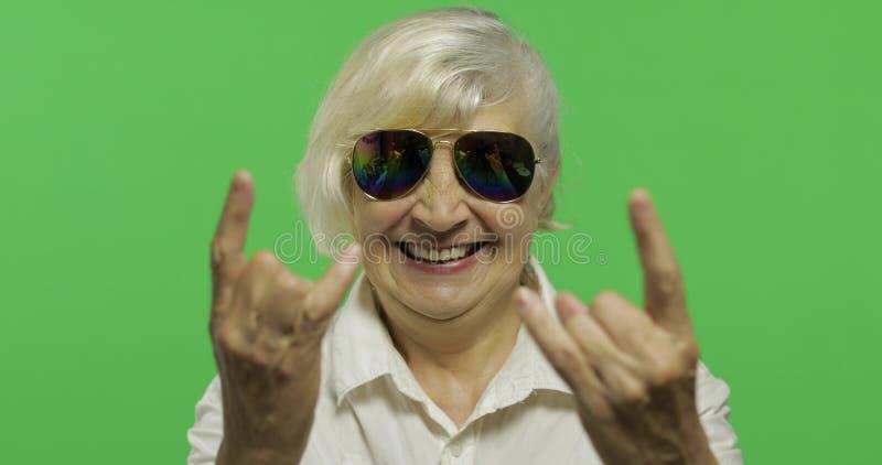 Een bejaarde toont teken van de hoornen met haar handen Twee in: 1 stock afbeelding