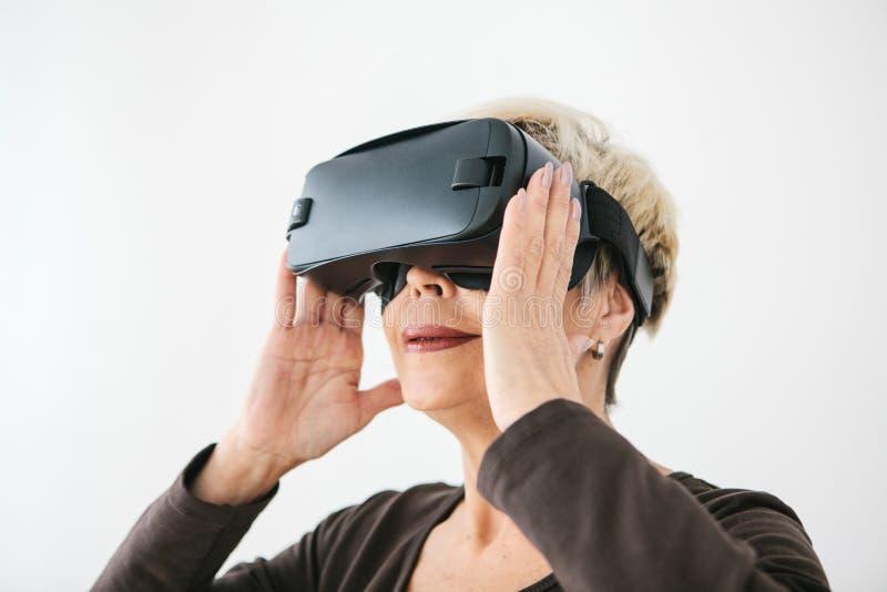 Een bejaarde in virtuele werkelijkheidsglazen Een bejaarde persoon die moderne technologie gebruiken royalty-vrije stock fotografie