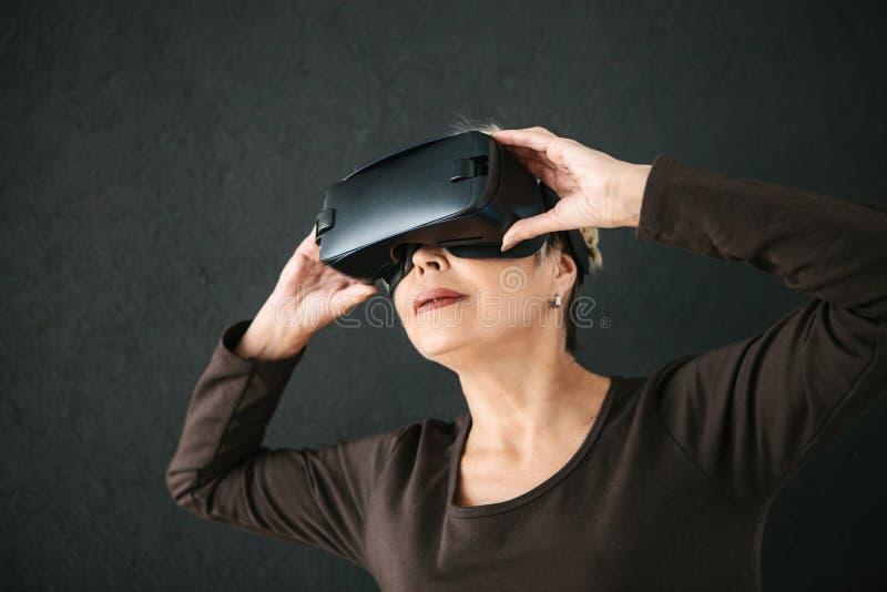 Een bejaarde in virtuele werkelijkheidsglazen Een bejaarde persoon die moderne technologie gebruiken stock foto's