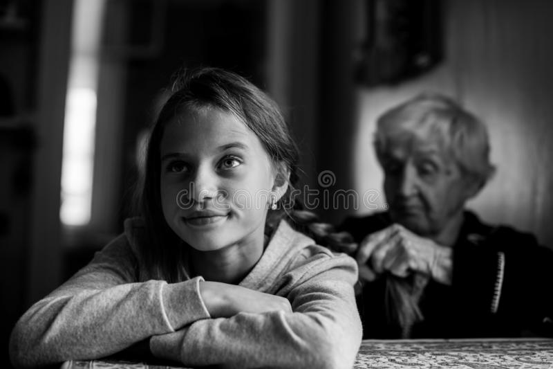 Een bejaarde vlecht het haar van haar kleindochter royalty-vrije stock foto's