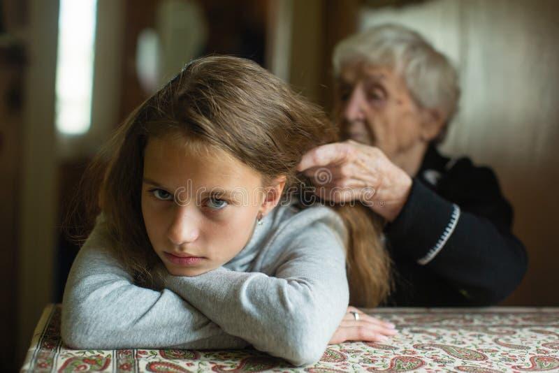 Een bejaarde vlecht het haar van haar kleindochter Familie royalty-vrije stock fotografie