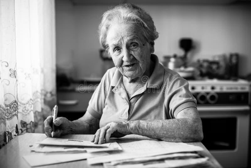 Een bejaarde vult de rekening voor betaling van de nutsdiensten hulp stock fotografie