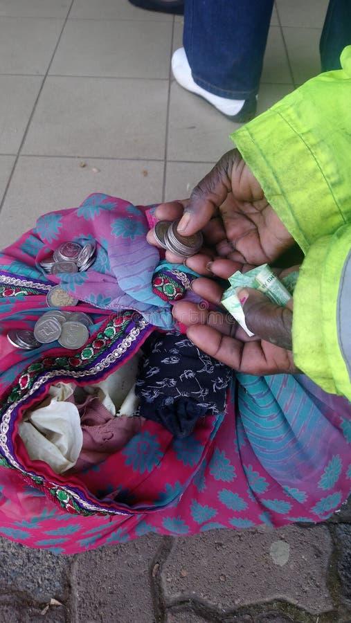 Een bejaarde woman& x27; s handen aangezien zij haar geld terwijl het wachten in een rij telt stock foto's