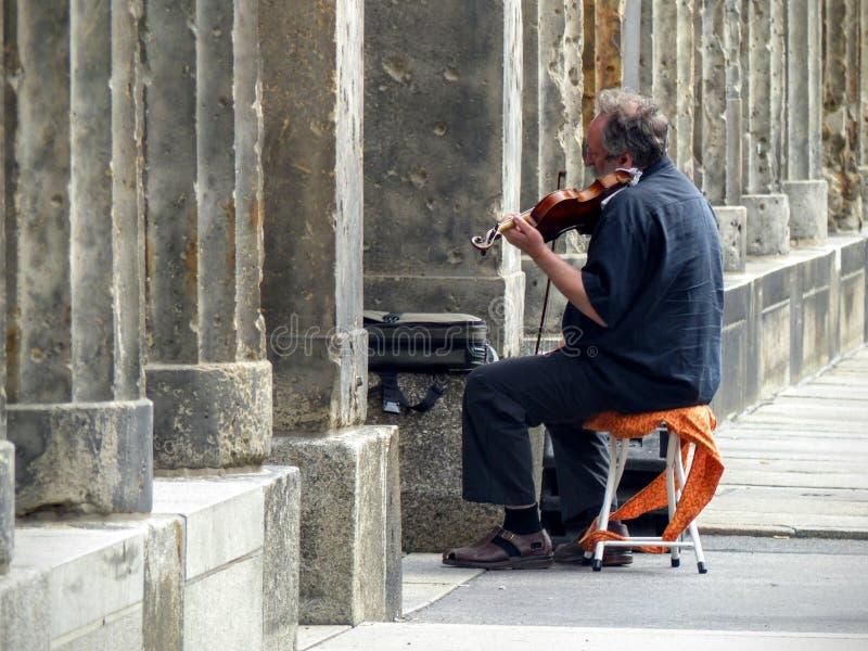 Een bejaarde zat op een kruk die de viool naast van de kolommen aan het eiland van de Musea aan Berlijn, Duitsland speelt stock afbeelding