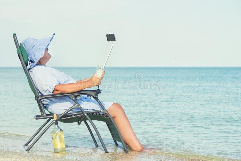 Een bejaarde zit op het strand op een chaise-longue, het drinken wijn en het maken van foto tegen de achtergrond van het overzees stock foto's