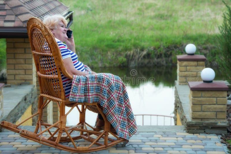 Een bejaarde zit in een rieten schommelstoel en het spreken op een celtelefoon Goede Mededeling Ontspan in een buitenhuis royalty-vrije stock foto
