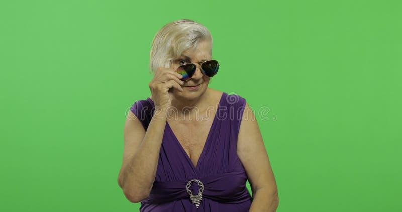 Een bejaarde in zonnebrilglimlachen Oude Grootmoeder Twee in: 1 stock foto's