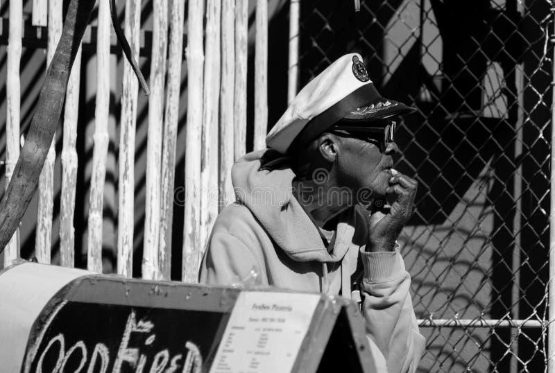 Een bejaarde zwarte mens met een zeeliedenhoed in de Kaap, Zuid-Afrika stock foto's