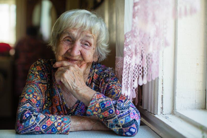 Een bejaardeportret - zit en kijkt uit het venster stock fotografie