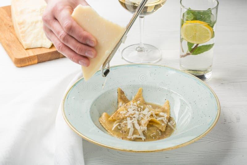 Een belangrijkste kok die meesterlijk heerlijke groene ravioli voorbereiden de roostersparmezaanse kaas van de kok` s hand op een stock afbeelding