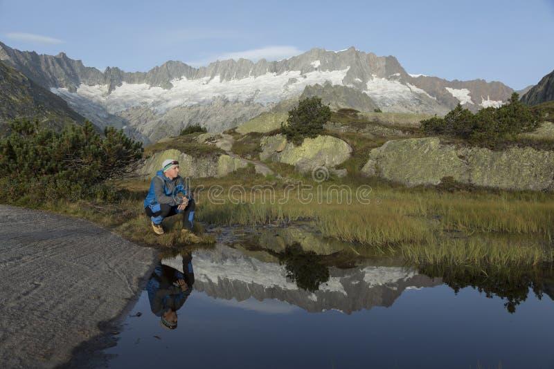 In een bergmeer wordt het landschap weerspiegeld een wandelaar maakt een onderbreking royalty-vrije stock fotografie