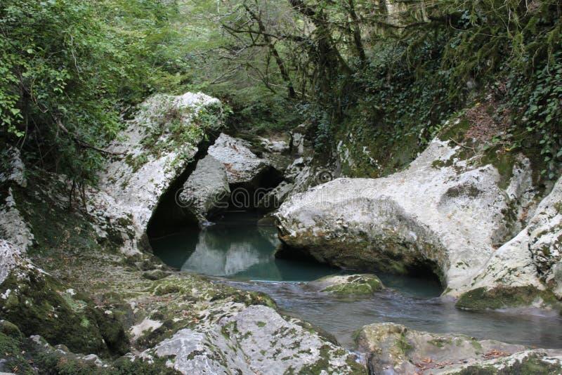 Een bergrivier met een waterval onder grote keien royalty-vrije stock fotografie