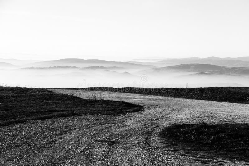 Een bergweg die op sommige verre bergen en heuvels richten stock foto's