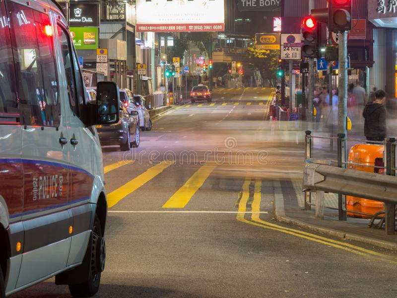 Een bestelwagen die van de Hong Kong-politie, zich voor het rode licht in Centrale de Weg van de Koningin bevinden stock afbeeldingen