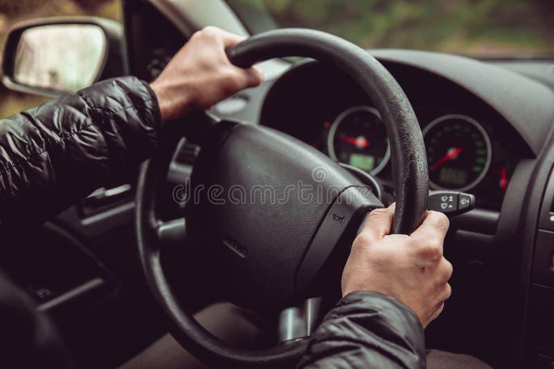 Een bestuurder in een auto voert taken noodzakelijk om het voertuig te sturen uit royalty-vrije stock foto