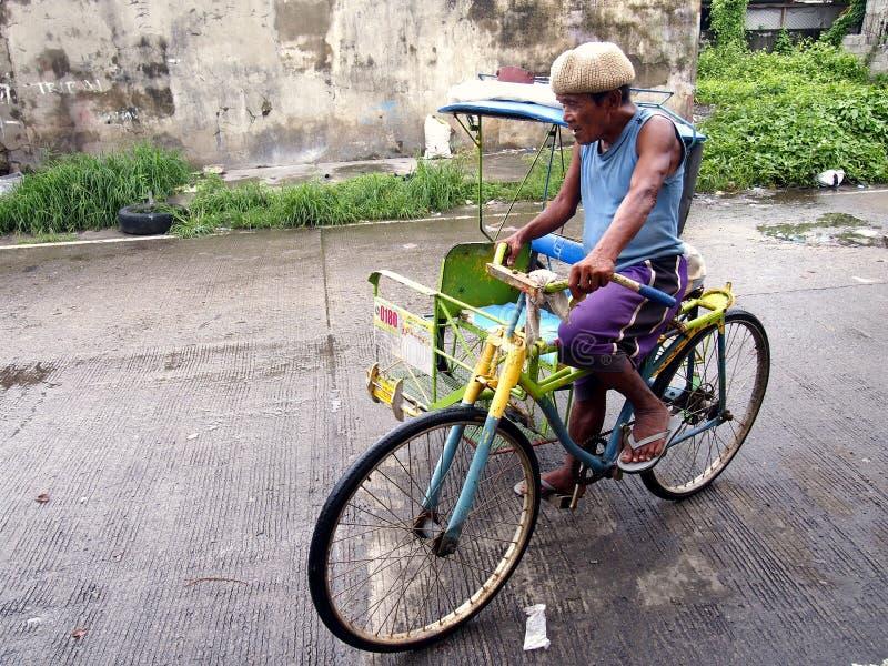 Een bestuurder in zijn die pedaal dreef driewieler aan, ook plaatselijk wordt gekend als pedicab stock afbeeldingen