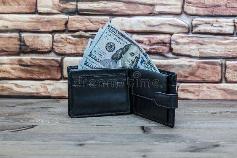 Een beurs met rekeningen van honderd dollars op een houten lijst aangaande een rode bakstenen muurachtergrond royalty-vrije stock foto