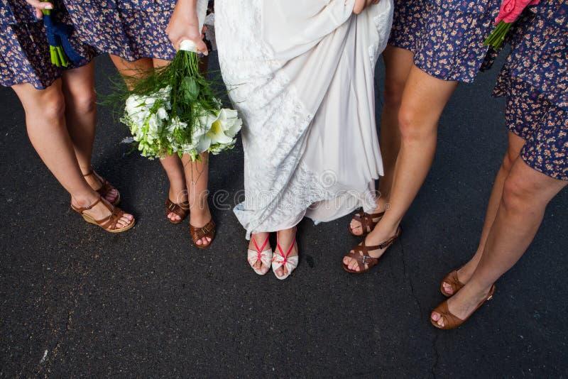 Een bevinden de bruids partijdames zich op een weg en tonen hun schoenen royalty-vrije stock afbeeldingen