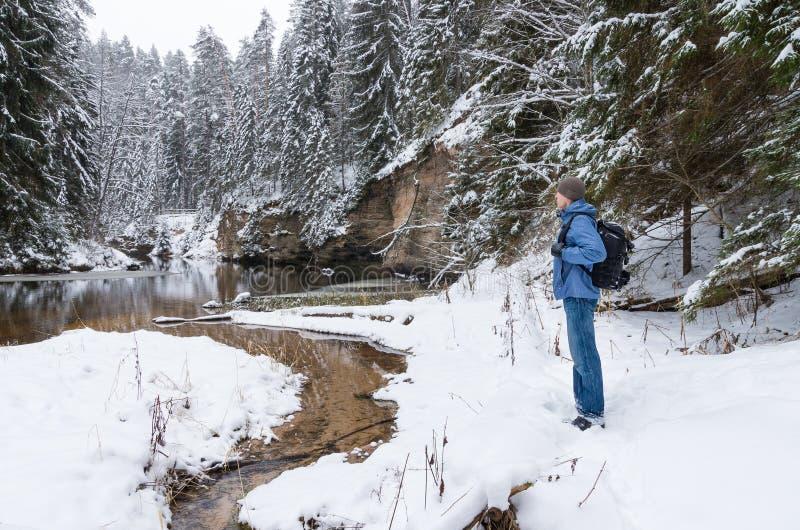 Een bevindende wandelaar door de de winterrivier stock afbeeldingen