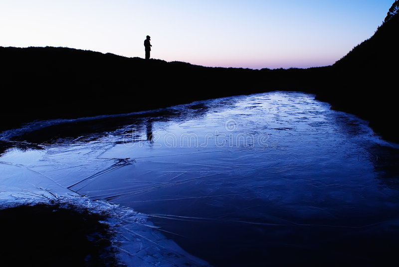 Een bevroren meer met een man silhouet stock afbeeldingen