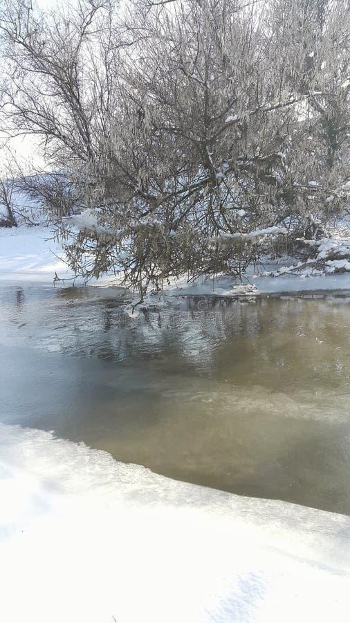 Een bevroren rivier in gevangenschap dichtbij de koude Sneeuw en blauwe hemel met wolken en stok Ik houd van op een bevroren rivi royalty-vrije stock afbeelding