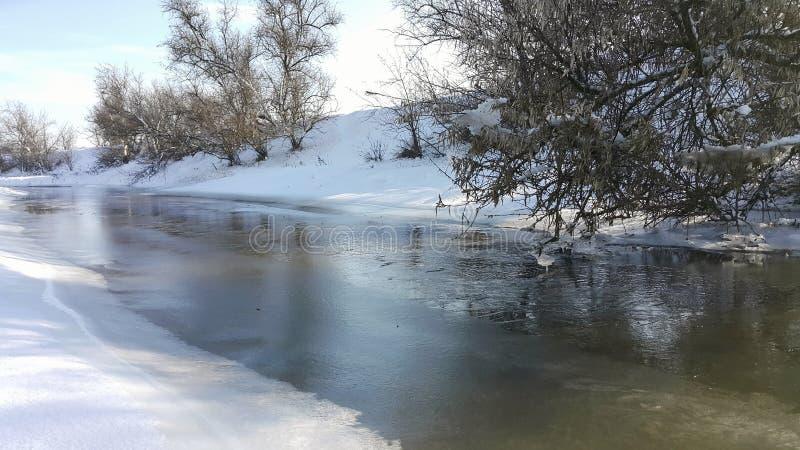 Een bevroren rivier in gevangenschap dichtbij de koude Sneeuw en blauwe hemel met wolken en stok Ik houd van op een bevroren rivi stock foto's
