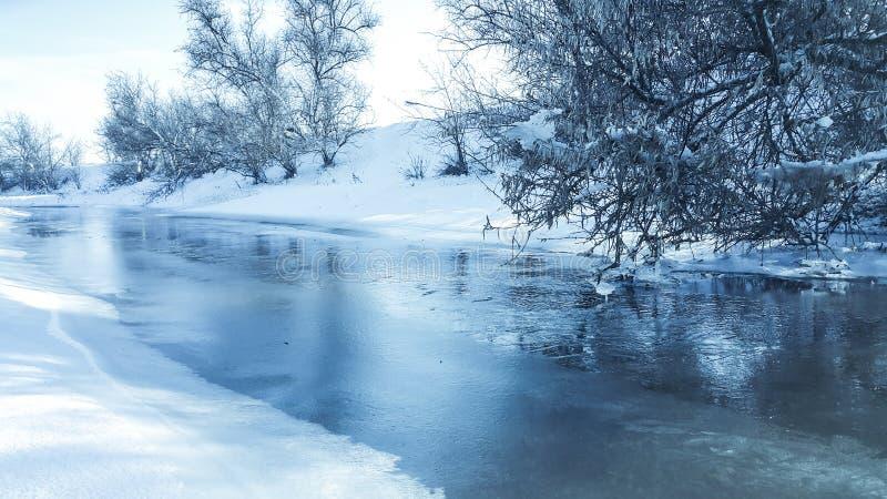 Een bevroren rivier in gevangenschap dichtbij de koude Sneeuw en blauwe hemel met wolken en stok Ik houd van op een bevroren rivi royalty-vrije stock foto's