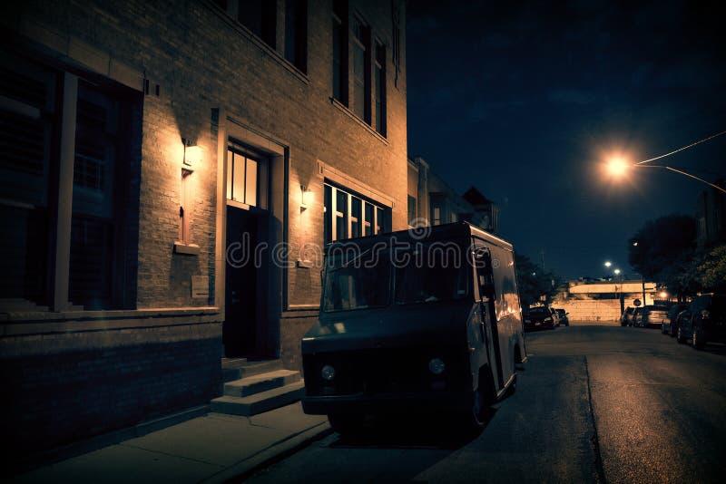 Een bewapende die veiligheidsvrachtwagen in een donkere stadsstraat bij nachtne wordt geparkeerd stock foto