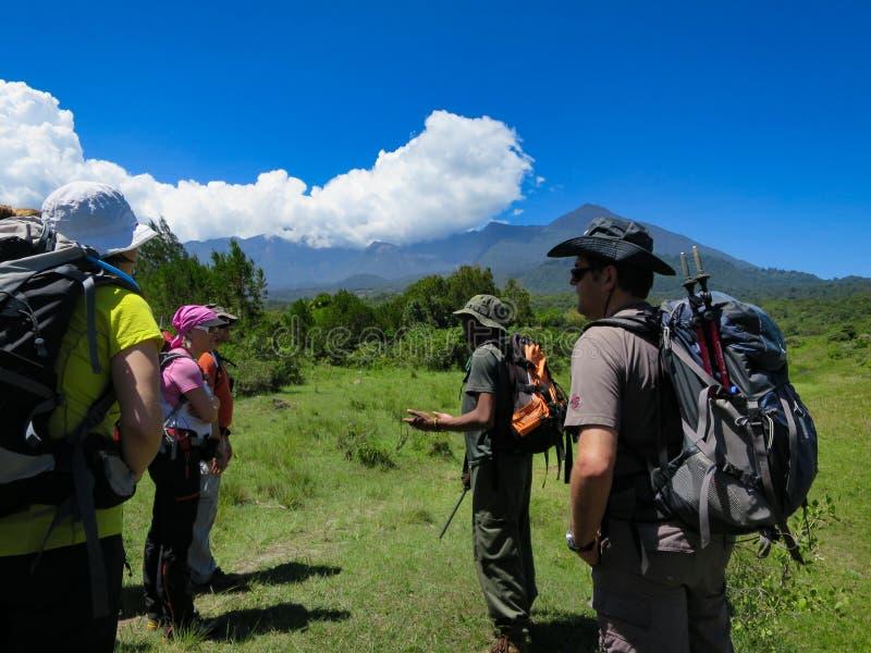 Een bewapende nationale parkboswachter instrueert Europese toeristen over de gevaren en de regels in het Nationale Park van Arush royalty-vrije stock fotografie