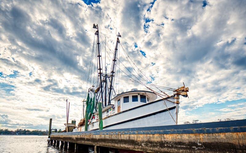 Een bewolkte blauwe die hemel achter een garnalenboot bij dok vanuit een lage invalshoek wordt genomen stock fotografie