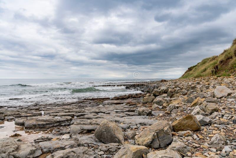 Een bewolkte dag op een steenachtig strand royalty-vrije stock foto