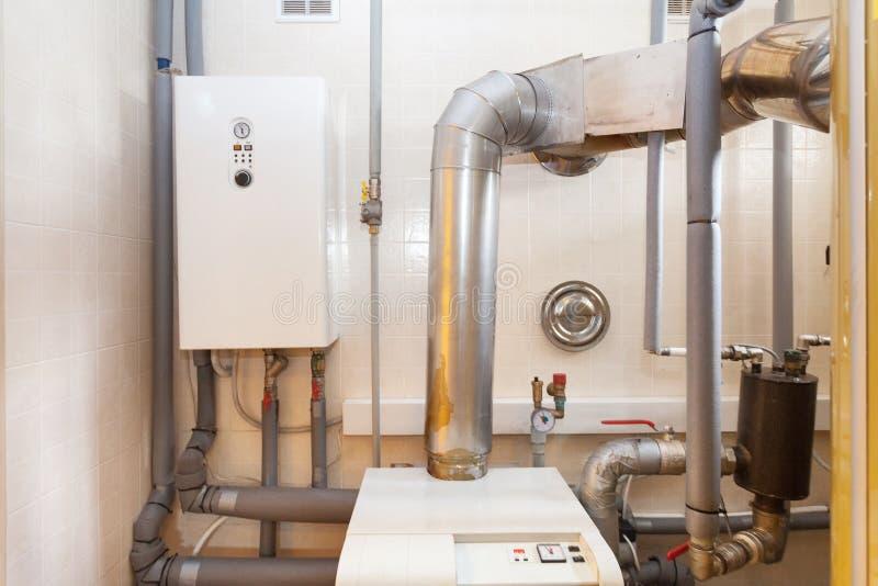 Een binnenlands huishoudenketelruim met een nieuwe moderne vaste brandstofboiler, het verwarmen elektrische warme watersysteem en royalty-vrije stock afbeelding