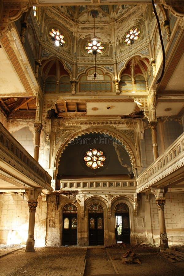 Een binnenlandse mening van een verlaten Hebreeuwse Joodse synagoge gebaad in stralen van licht royalty-vrije stock foto's