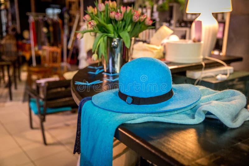 Een blauw breed-brimmed dame` s hoed en een met de hand gemaakte sjaal stock afbeelding