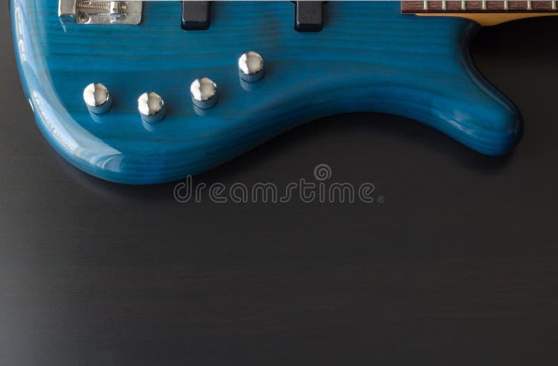Een blauwe basgitaar omhoog een gainst een zwarte houten achtergrond stock afbeelding
