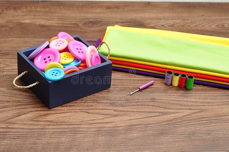 Een blauwe die container met knopen, broodjes wordt gevuld van draad en een stapel van kleurrijk materiaal stock foto's