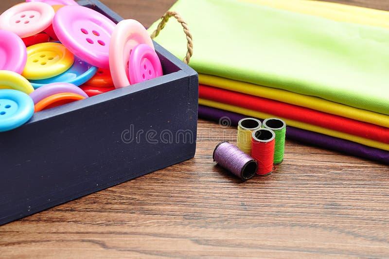 Een blauwe die container met knopen, broodjes wordt gevuld van draad en een stapel van kleurrijk materiaal royalty-vrije stock foto